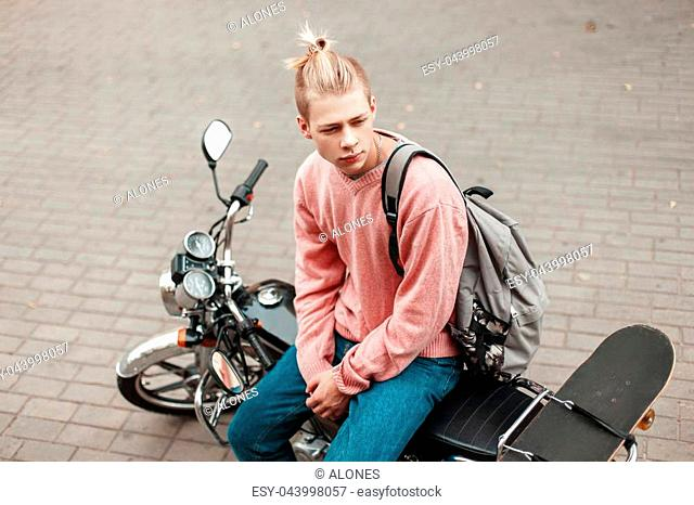 Handsome man with a hairstyle in a pink sweater with a skateboard and a backpack sitting on a motorcycle