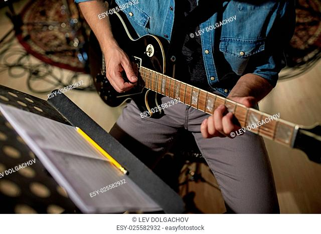 people, musical instruments and entertainment concept - male guitarist playing electric guitar with music book on stand at studio