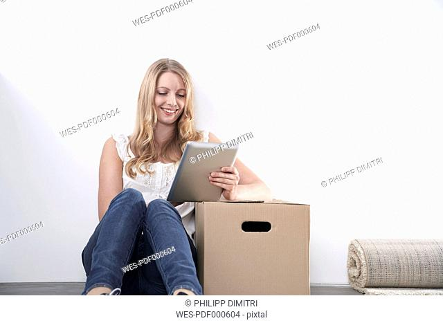 Smiling young woman with cardboard box and tablet computer