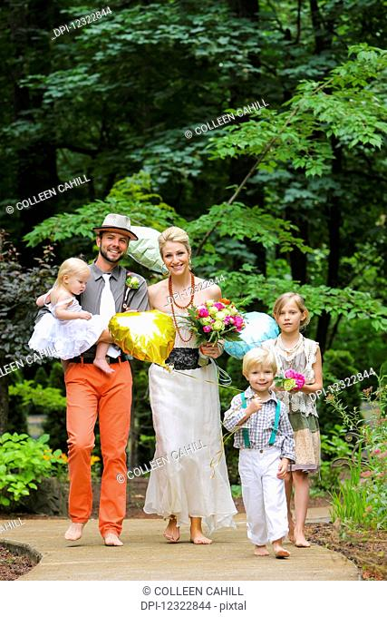 Portrait of a family dressed in formal wear walking down a paved trail in bare feet; Oregon, United States of America