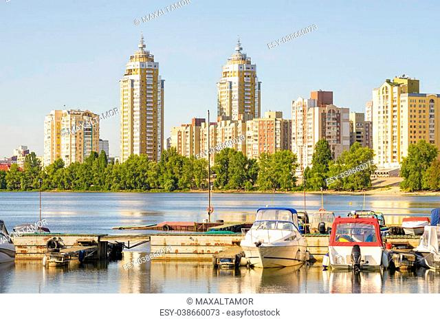 Some boats are parked on the Dnieper River in Kiev, Ukraine. High buildings of the city appears in the background