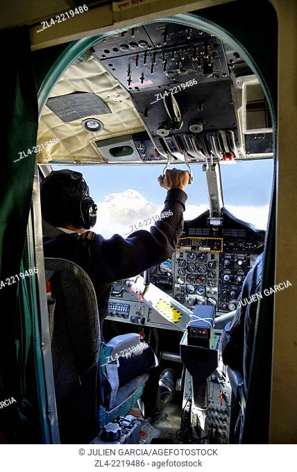 Pilot in the cockpit of a small twin otter aircraft and view of the Dhaulagiri summit (8167m). Nepal, Gandaki, flight between Pokhara and Jomsom in Mustang