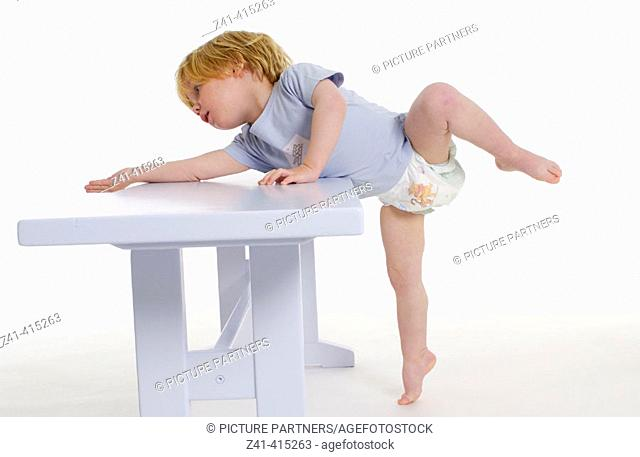 Toddler hanging over a bench