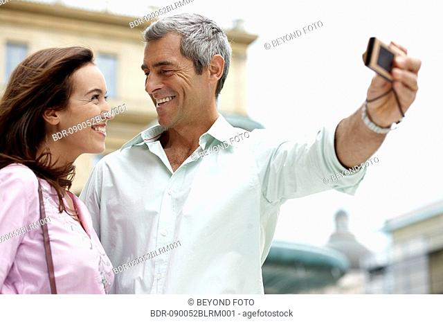 couple on vacation taking picture of themselves with digital camera