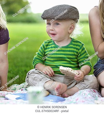 Boy eating rice cake at picnic
