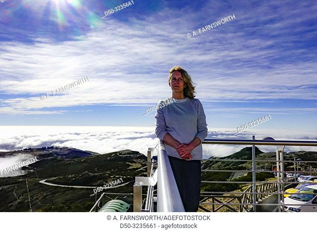 Madeira, Portugal A woan poses at pico do Arieiro, an 1800 meter peak in the centerof the island above the clouds