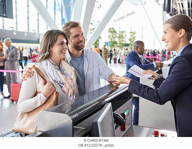Customer service representative helping couple at airport check-in counter