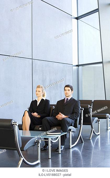 Two job candidates sitting in a waiting room