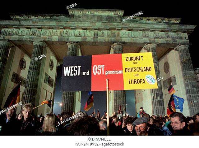 A poster with the print 'West and East - Future for Germany and Europe' is held up in front of Brandenburg Gate in Berlin in the night to 03 October 1990