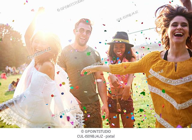 Young adult friends throwing and dancing in confetti at Holi Festival