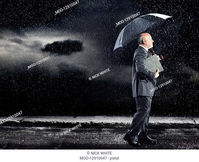 Businessman Walking in rain under umbrella side view
