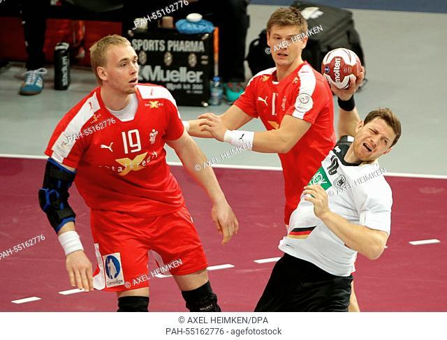 Denmarks's Rene Toft Hansen (l-r), Denmarks's Lasse Swan and Germany's Martin Strobel challenge for the ball during the men's Handball World Championship 2015...