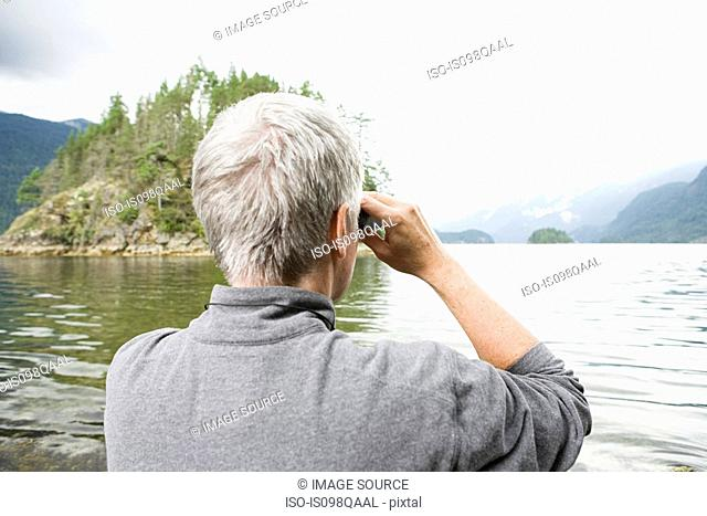 Man looking at fjord with binoculars