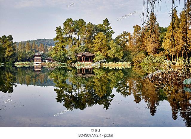 Mirror image of trees and traditional buildings on Westlake, Hangzhou, China