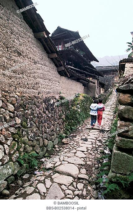 View of children walking on pathway by house, Taishun County, Zhejiang Province, People's Republic of China