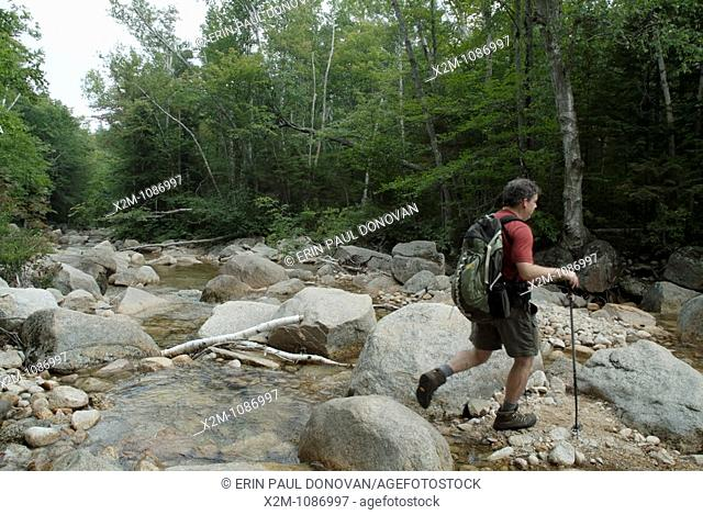 A hiker crosses Sawyer River on Hancock Notch Trail during the summer months  Located in the White Mountains, New Hampshire USA