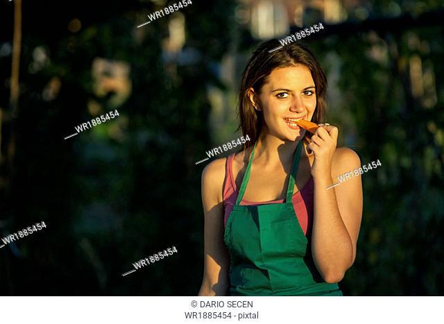 Young Woman In Garden Eating Carrot, Croatia, Slavonia, Europe