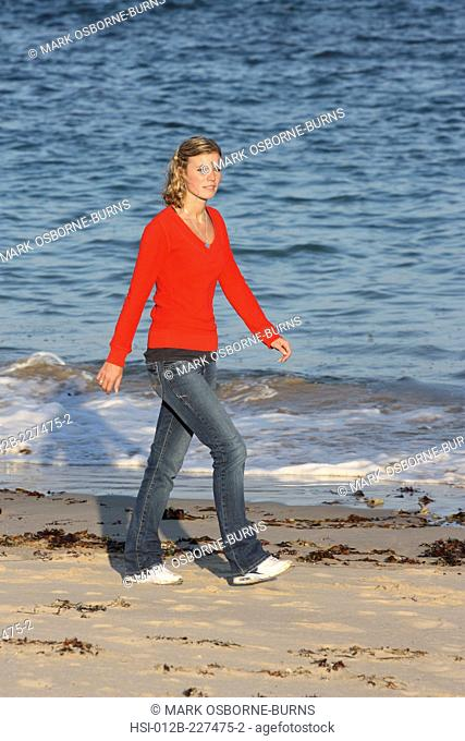 Young blonde woman outdoors walking on the beach