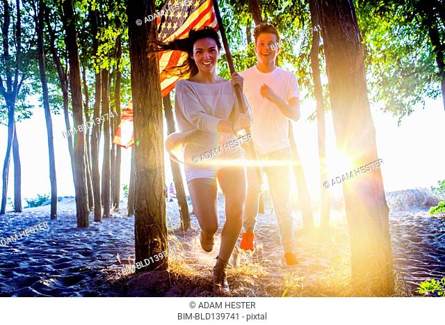Caucasian couple carrying American flag in trees on beach