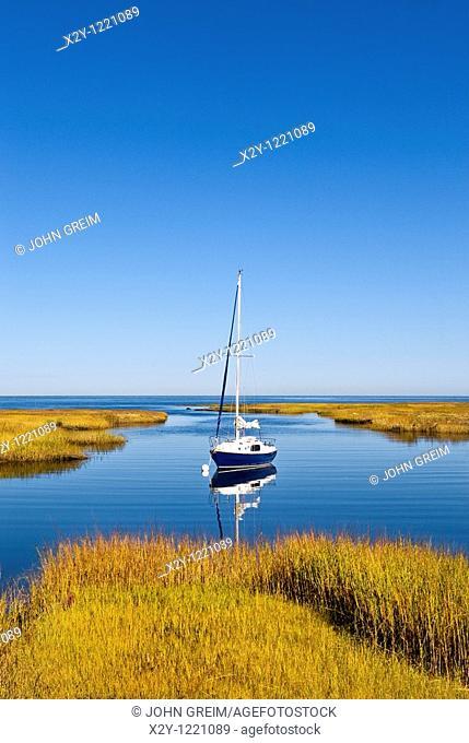 Sailboat anchored in a salt marsh leading into Cape Cod Bay, Cape Cod, MA, Massachusetts