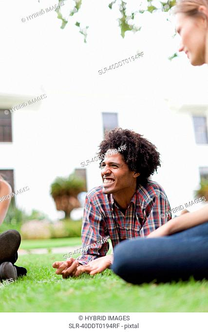 Students relaxing on grass on campus