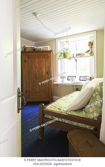 Guest bedroom with wood-frame single bed and old wooden armoire inside an old 1862 cottage style home