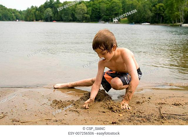 boy playing on a sany beach in cottage country