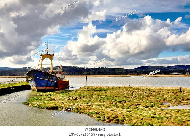 Weathered and brightly painted boat afloat on the incoming tide in the Nith Estuary, Glencaple, Dumfries and Galloway, on a winters day