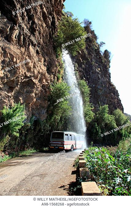 local bus crossing waterfall at the old coastal road, also called the car washing street, Madeira, Portugal, Europe
