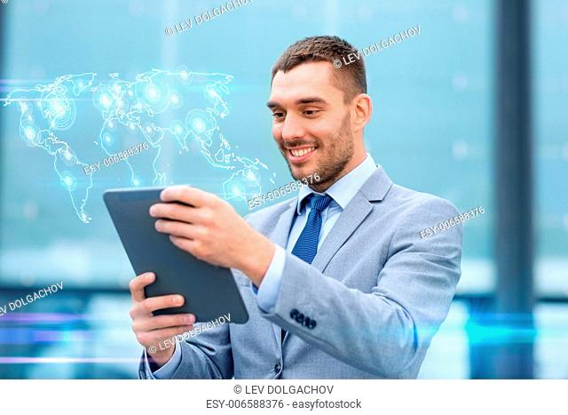 global business, education, technology and people concept - smiling businessman working with tablet pc computer and world map hologram on city street