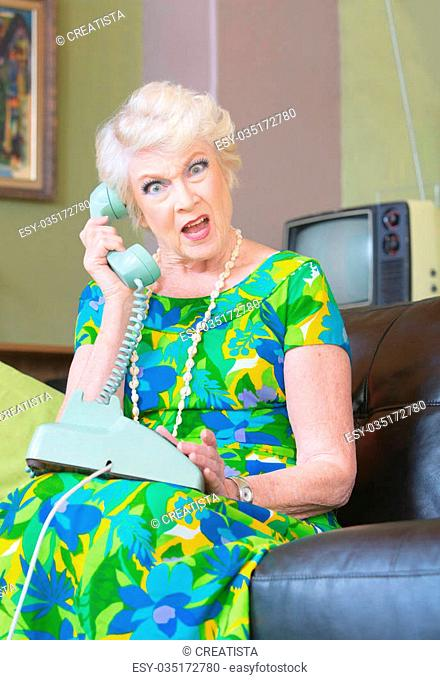 Angry European senior female on phone in 1960s fashion