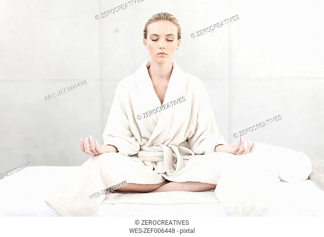 Young woman with bathrobe meditating