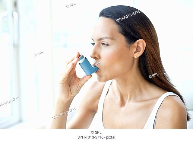 MODEL RELEASED. Young woman using an inhaler