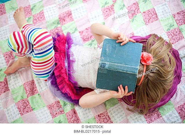 Girl reading book on blanket