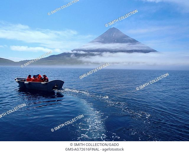 Scientists from the Islands of Four Mountains science project headed ashore by skiff on the first day of fieldwork. In the backdrop is Cleveland volcano