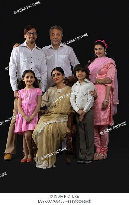 Portrait of smiling Indian multi-generation family dressed in retro style