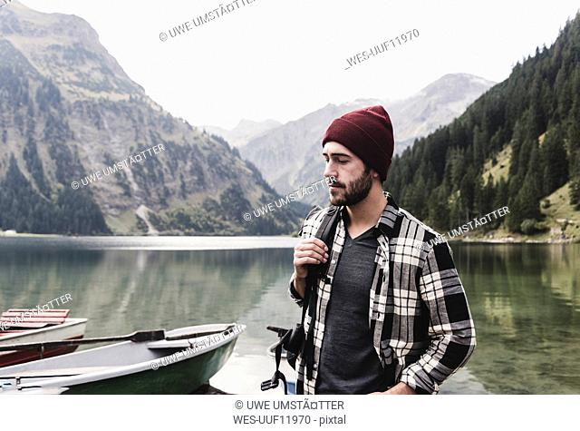 Austria, Tyrol, Alps, serious man at mountain lake