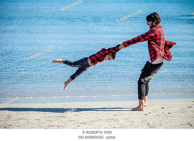 Father and son on beach, father holding son's hands, swinging him around