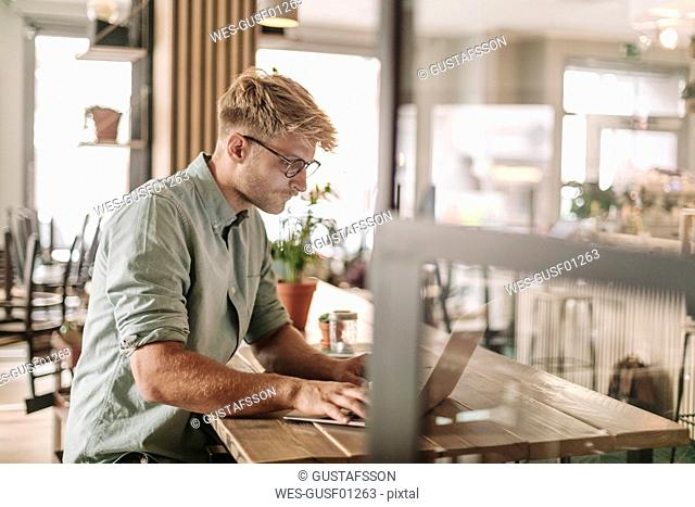 Young man working in his start-up cafe, using laptop