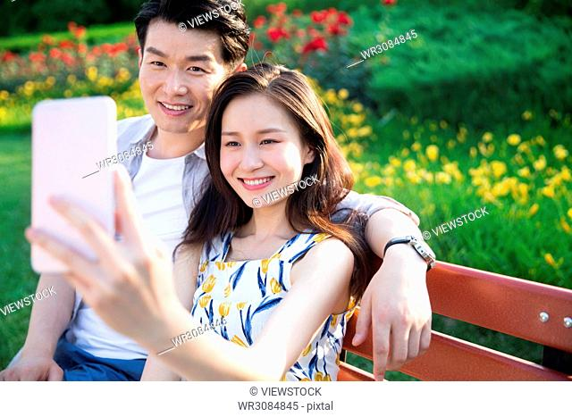Young couples take pictures with their mobile phones