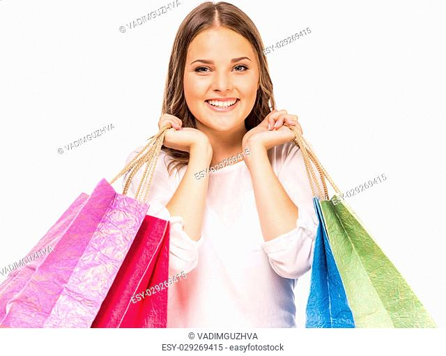Happy woman holding many colored shopping bags in two hands on white background