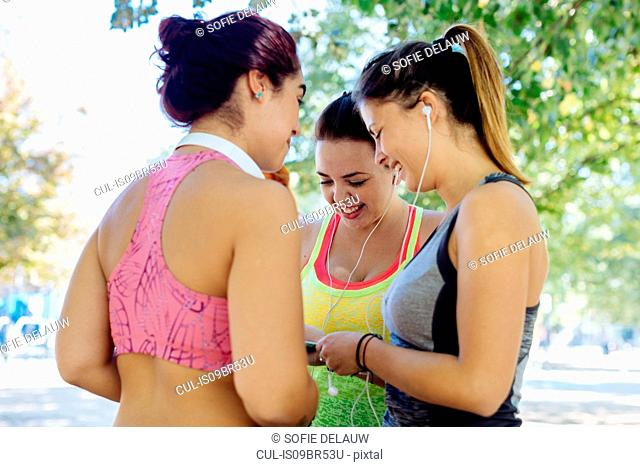 Friends exercising and using cellphone in park