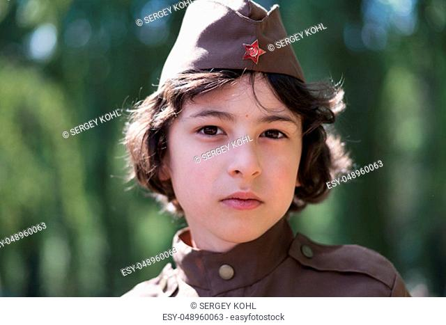 Portrait of a boy in the uniform of a soldier of the Red Army during the Second World War. Face close up