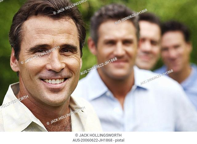Portrait of a mature man smiling with his friends in the background