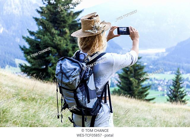Germany, Bavaria, Oberammergau, young woman hiking taking a cell phone picture on mountain meadow