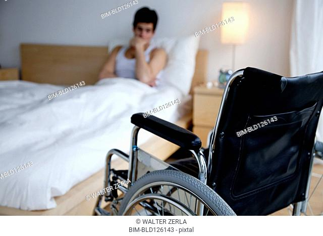 Disabled Caucasian man in bed out of reach of wheelchair