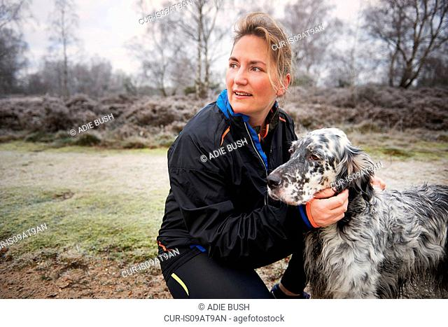 Mature woman crouching down stroking dog looking away