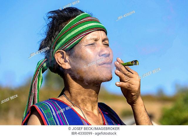 Man in traditional costume smoking cigar, Phnong tribe, ethnic minority, Pnong, Bunong, Senmonorom, Sen Monorom, Mondulkiri Province, Cambodia