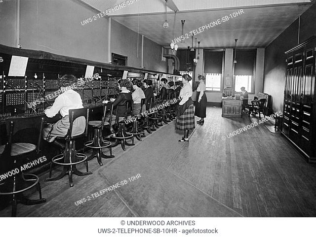 United States, c. 1915 A telephone switchboard with operators connecting the calls and two supervisors standing in back and overseeing them