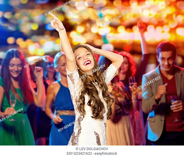 people, holidays and nightlife concept - happy young woman or teen girl in fancy dress with sequins and long wavy hair dancing at night club party over crowd...